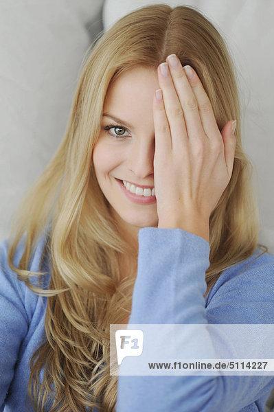 Lächelnde Frau  die ein Auge bedeckt