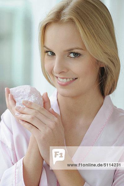 Lächelnde Frau mit Rosenquarz in der Hand