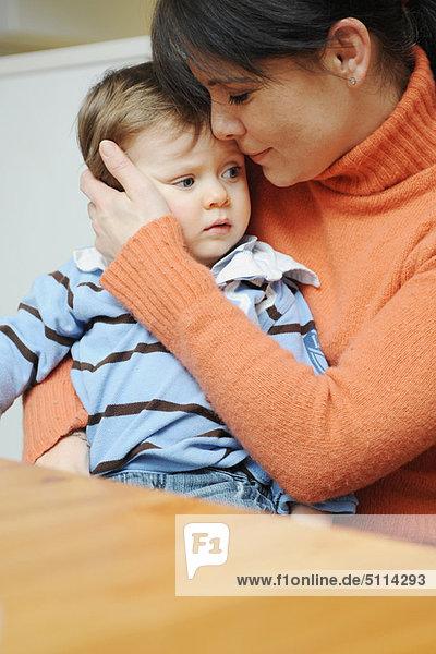 Mutter umarmt Kleinkind Sohn bei Tisch