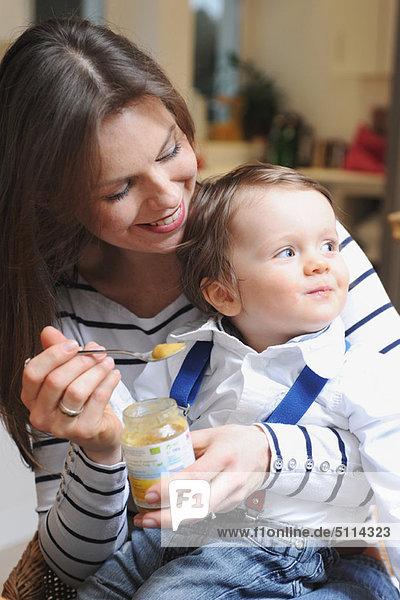 Frau füttert Kleinkind Sohn Babynahrung