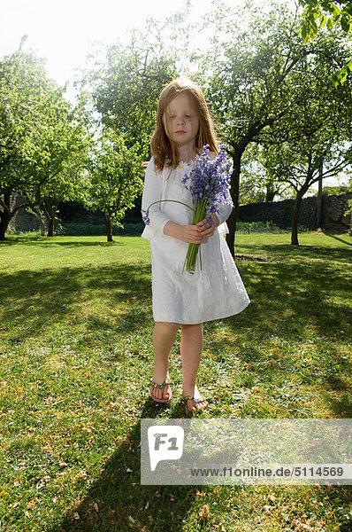 Girl holding flowers in backyard