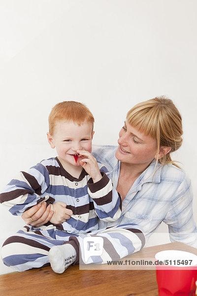 Mutter und Sohn im Pyjama bei Tisch