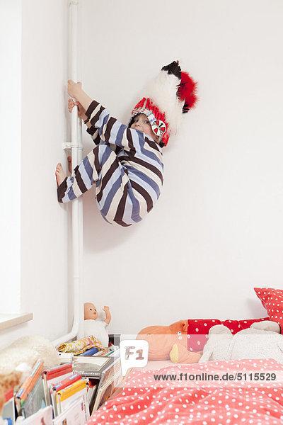 Junge mit Kriegshaube klettert die Wände hoch