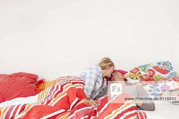 Pärchenküssen im Bett