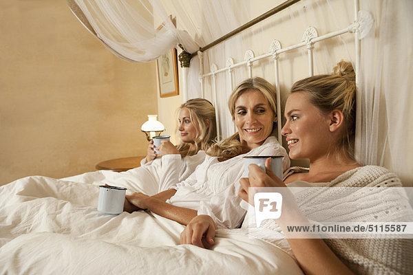 Mutter und Töchter mit Kaffee im Bett