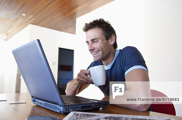 Mann mit Laptop und Tasse Kaffee