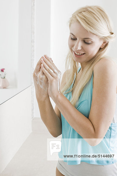 Woman creaming hands