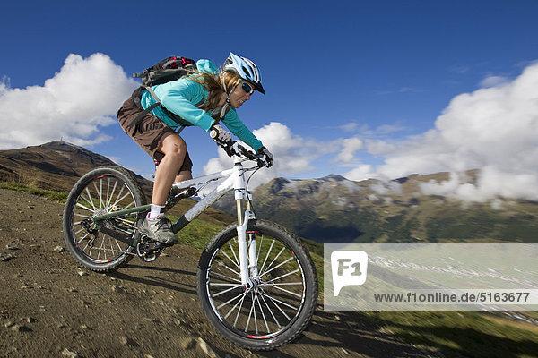 Italien  Livigno  Blick auf eine Frau beim Mountainbikefahren