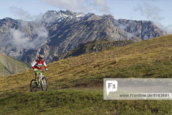 Italien  Livigno  Blick auf die Frau beim Mountainbike fahren bergauf