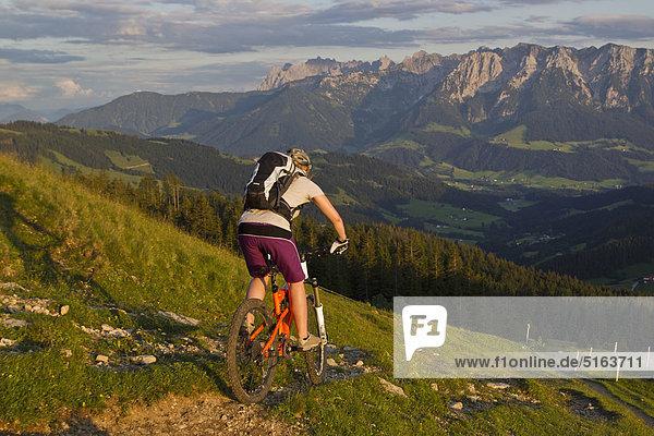 Österreich  Tirol  Spitzstein  Junge Frau Mountainbiken am Hang mit Kaisergebirge im Hintergrund