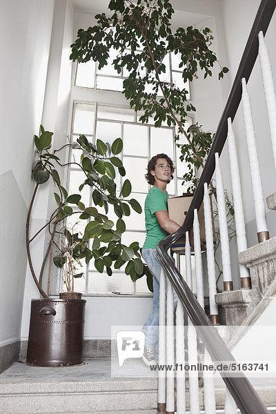 Junger Mann mit Karton auf der Treppe bei der Renovierung der Wohnung