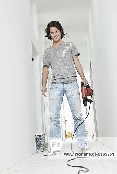Junger Mann mit Elektrobohrer in renovierender Wohnung