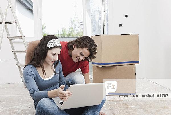 Deutschland  Köln  Junges Paar mit Laptop in renovierter Wohnung