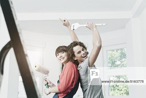 Deutschland  Köln  Junges Paar Malerei in renovierender Wohnung Deutschland, Köln, Junges Paar Malerei in renovierender Wohnung