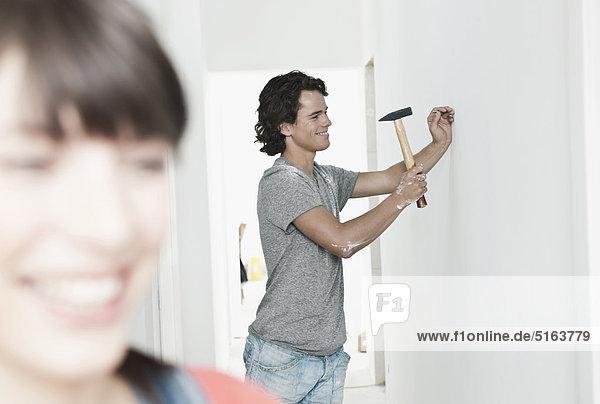 Junger Mann hämmert Nagel in renovierender Wohnung mit Frau im Vordergrund