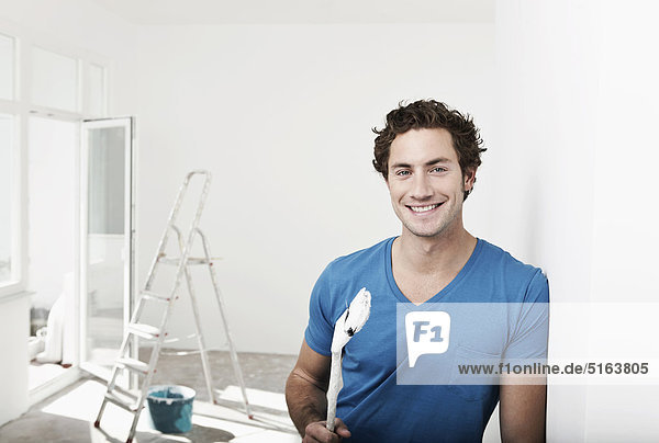 Close up of young man holding paint brush in renovating apartment  smiling  portrait