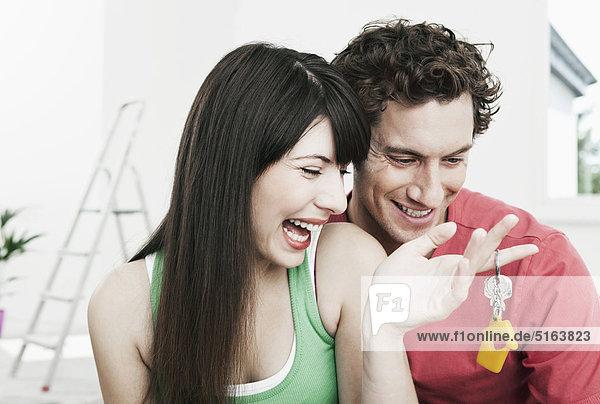Deutschland  Köln  Nahaufnahme eines jungen Paares mit Hausschlüssel in einer renovierten Wohnung  lächelnd