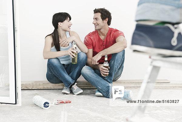 Deutschland  Köln  Junges Paar macht Pause in renovierter Wohnung