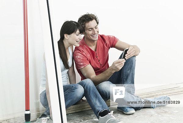 Deutschland  Köln  Junges Paar beim Betrachten von Handybildern in der renovierten Wohnung