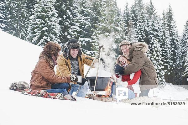 Österreich  Salzburger Land  Flachau  Junge Männer und Frauen sitzen am Kamin und kochen Tee im Schnee