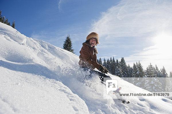 Österreich  Salzburger Land  Flachau  Junge Frau beim Rodeln im Schnee