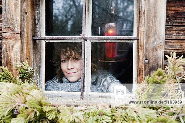 Österreich  Salzburger Land  Flachau  Junge Frau im Winter durchs Fenster blickend