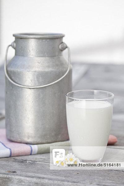 Deutschland  Nahaufnahme von Milchkanne und Milchglas auf Holztisch
