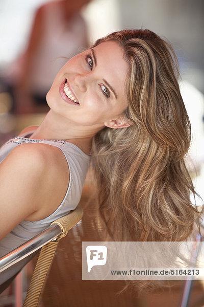 Nahaufnahme einer jungen Frau im Straßencafé  lächelnd  Portrait