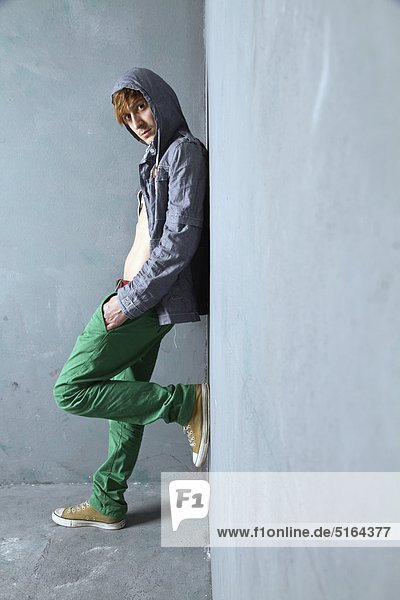 Junger Mann stehend und lehnend gegen die schmutzige Wand  Portrait Junger Mann stehend und lehnend gegen die schmutzige Wand, Portrait