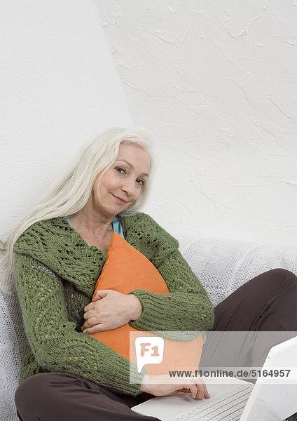Frauenumarmungskissen neben Laptop auf Sofa