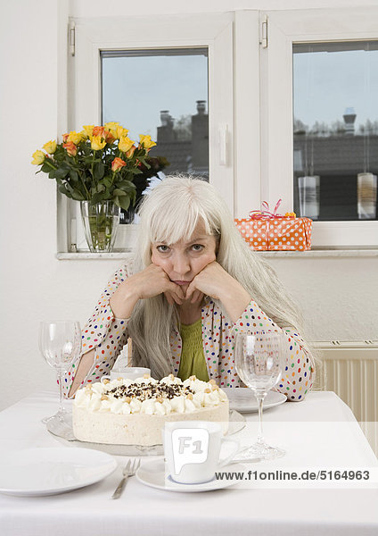 Frau am Esstisch sitzend mit Kuchen  Flowervase und Geschenk  Portrait