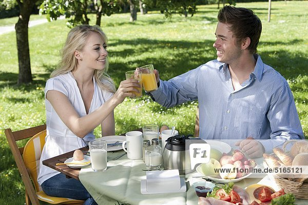 Junges Paar frühstückt im Park