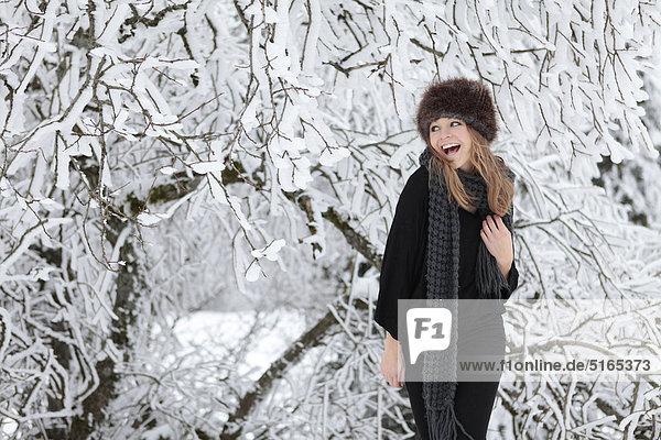 Junge Frau mit Schal und Mütze im Schnee