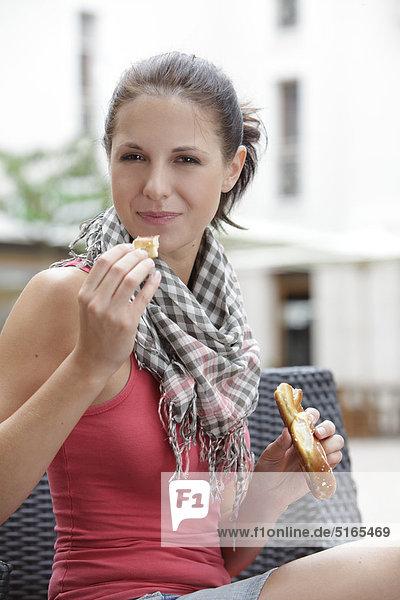 Junge Frau isst Brezel