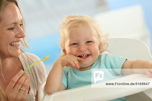 Mutter füttert lachendes Baby