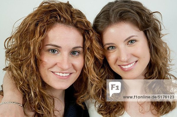 Two young women smiling and looking at the camera Close view