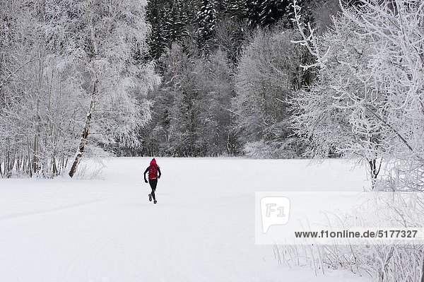 A jogger running throught a snowy winter landscape