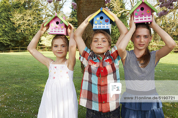 Kinder mit Vogelhäuschen im Hinterhof