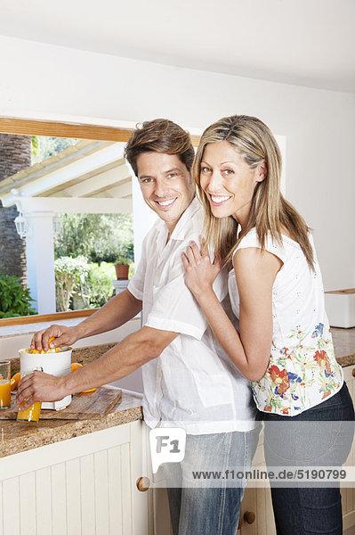 Paar mit Entsafter in der Küche