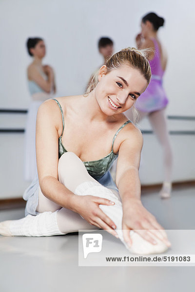 Ballet dancer stretching in studio