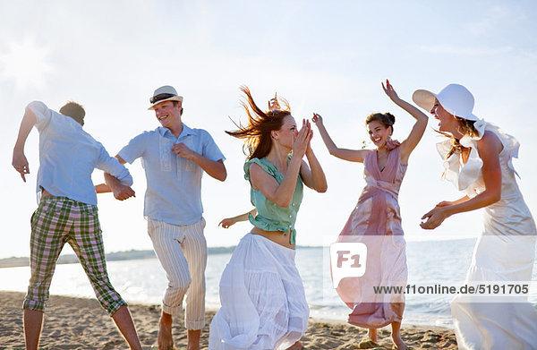 Menschen tanzen zusammen am Strand Menschen tanzen zusammen am Strand