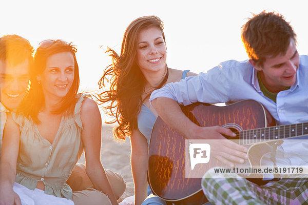 Mann spielt Musik für Freunde am Strand