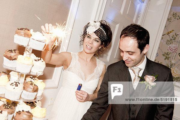 Frischvermähltes Paar mit Wunderkerze auf Kuchen