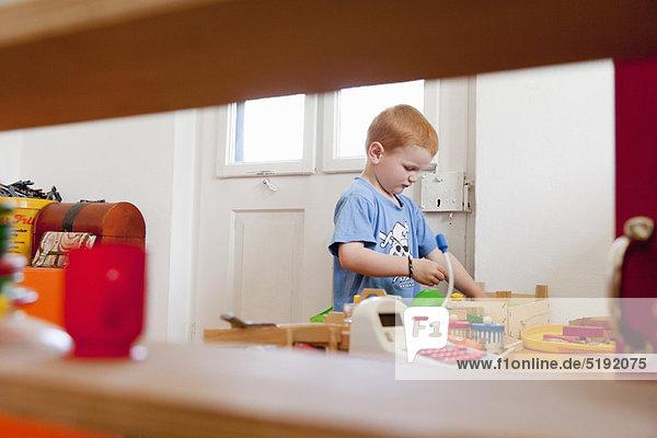 Junge spielt mit Spielzeug im Wohnzimmer