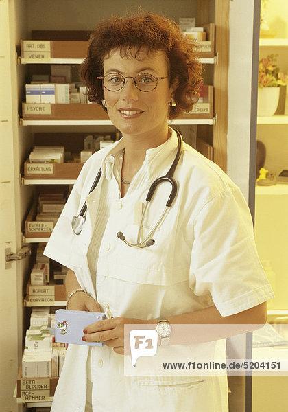 Ärztin vor Medikamentenschrank