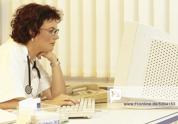Ärztin am Schreibtisch  vor Monitor