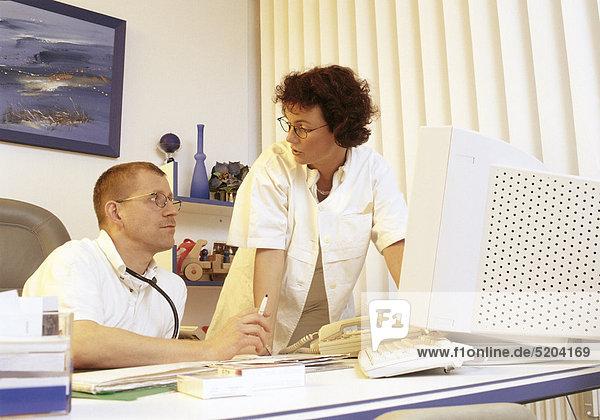 Arzt und Ärztin im Gespräch  am Schreibtisch