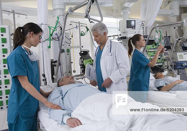 Intensivstation im Krankenhaus  Arzt und Krankenschwestern bei Patienten
