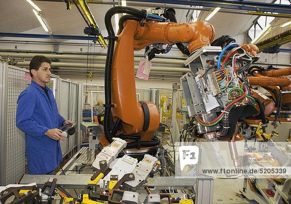 Techniker steuert Industrieroboter