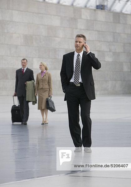 Zwei Männer und eine Frau gehen durch große Halle  ein Mann mit Handy